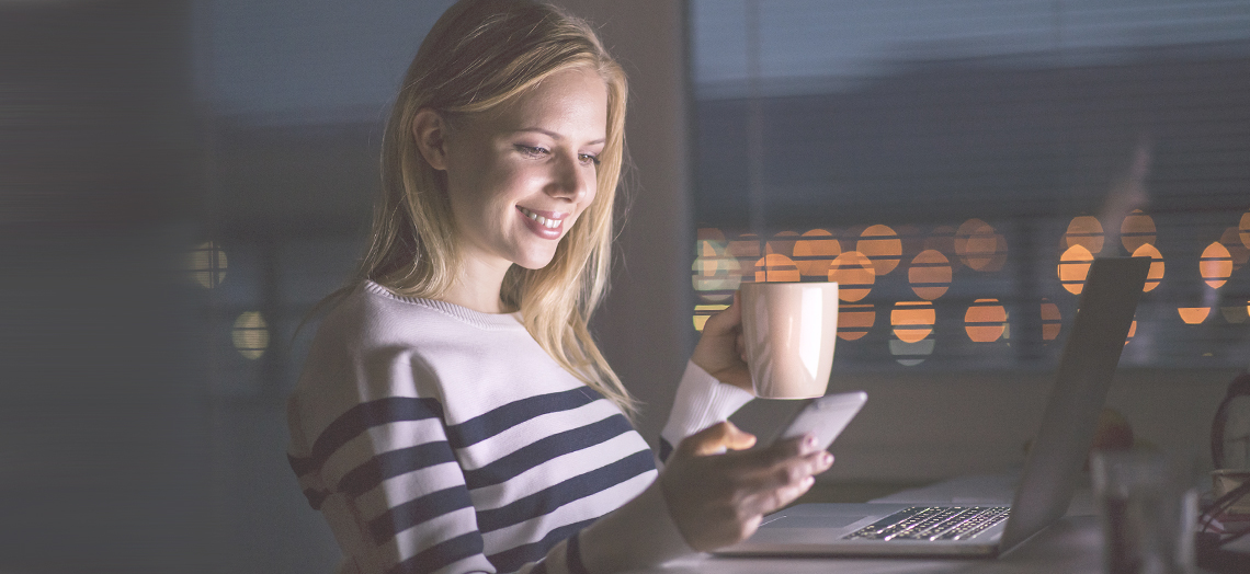Woman sat at desk with laptop on, smartphone in one hand, reading tips for becoming a self-employed blogger and a mug of tea in the other hand. It's night time and you can see a city scene out of the window.